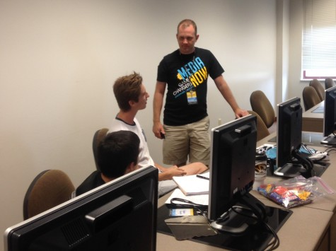 Instructor Jason Wallestad conferences with a student about his website. Wallestad
