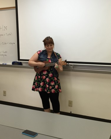 Devon Cahill playing her ukulele and singing for the class.
