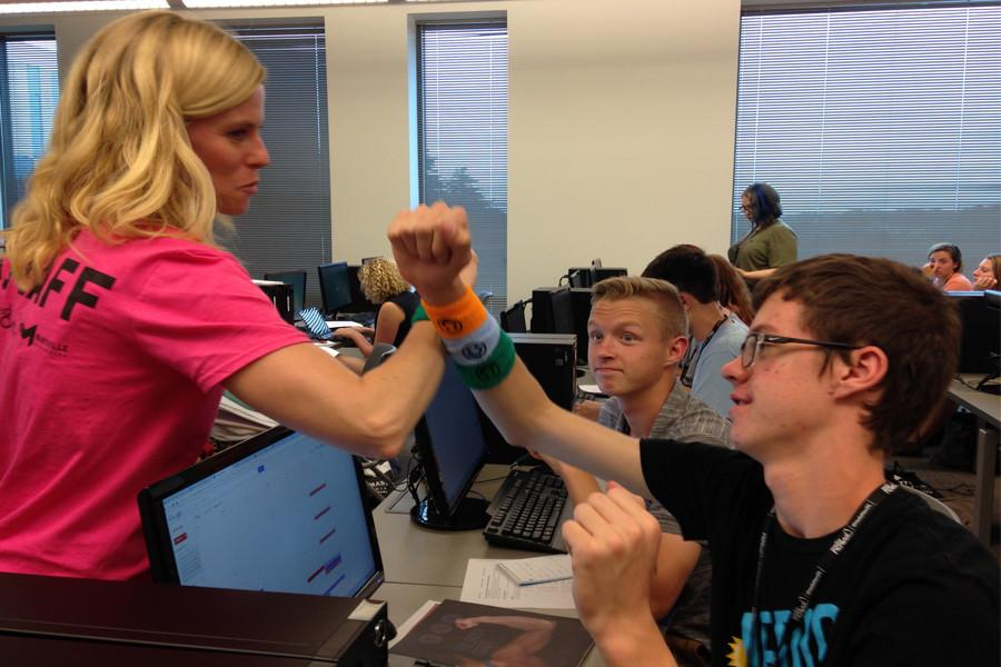 Workshop Director Kate Manfull creates a handshake with students in the EIC class.